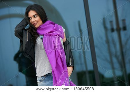 Portrait of Beautiful brunette young oriental beauty female  with black long hair Dressed in Leather jacket and denim pants with Oriental pink scarf and oriental jewelry.