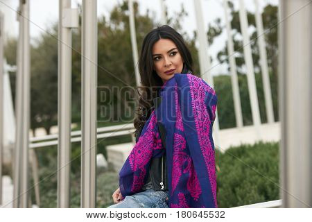 Portrait of Beautiful brunette young oriental beauty female  with black long hair Dressed in Leather jacket and denim pants with Oriental Multicolored scarf and oriental jewelry.