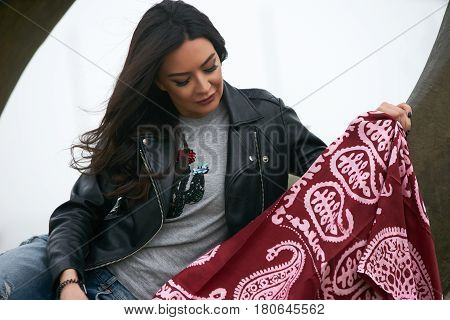 Portrait of Beautiful brunette young oriental beauty female  with black long hair Dressed in Leather jacket and denim pants with Oriental red scarf and oriental jewelry.