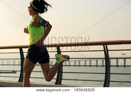 one young fitness woman running at seaside