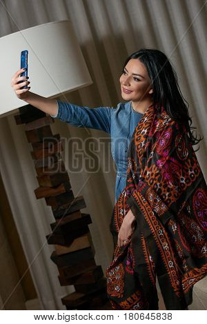 Portrait of a beautiful brunette doing selfie young oriental beauty female with black long hair Dressed in a denim dress clothing with Oriental Multicolored scarf and oriental jewelry.