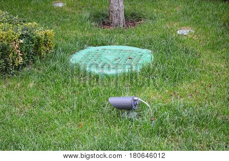 Manhole Sewer Cover with Garden Light Lanterns In Lawn. Solar Powered Lamp in the garden