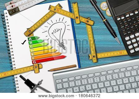 Wooden ruler on a desk in the shape of ecologic house with energy efficiency rating. Project of ecological house