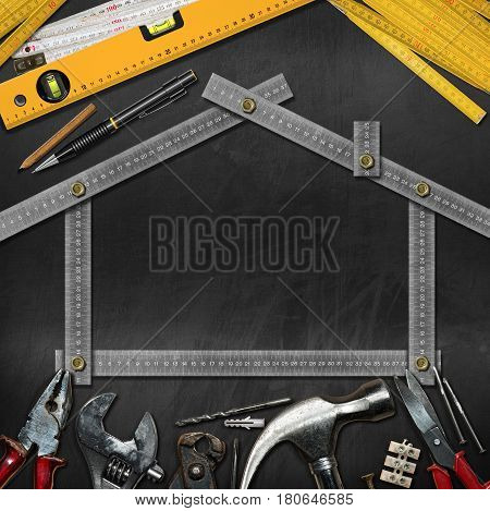 Home improvement concept - Metal ruler in the shape of a house on a blackboard with copy space and work tools