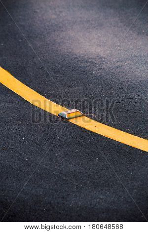 Curve Asphalt road with yellow reflector line.