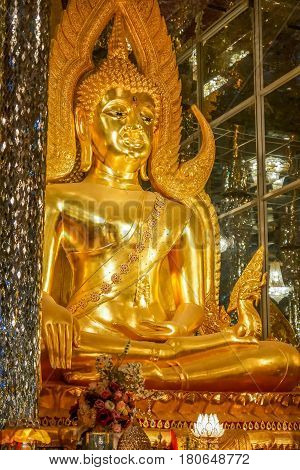 Golden Buddha image in church decorated with glass Thailand Buddhist temple