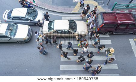Bangkok THAILAND - October 24 2016. top view of people are walking across road when the cars are stopping and blocking people at the crosswalk in business city.