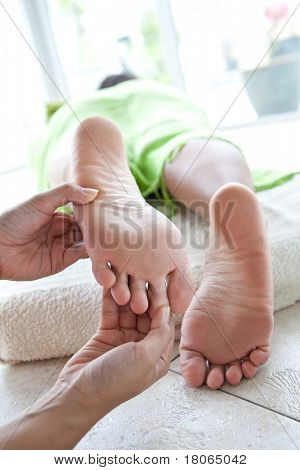 Woman receiving foot reflexology by therapist