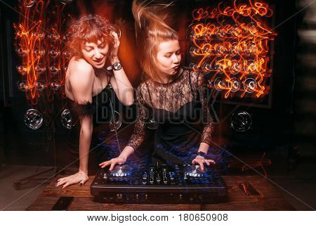 Two attractive beautiful disk jockey girls mix music on DJ console and enjoy dance party at nightclub. Fun, relax, nightlife, light long exposure