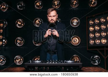 Professional bearded disk jockey at the console in studio ready to start music party. Nightclub, dance, famous rhythms, console.