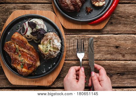 Appetizing beef steak with baked potato and onion rings, top view. Unrecognizable person having meal, hands holding knife an fork, free space