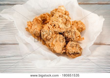 Appetizing baked breaded chicken in paper on white wooden table, flat lay. American fast food, tasty snack, traditional cuisine.