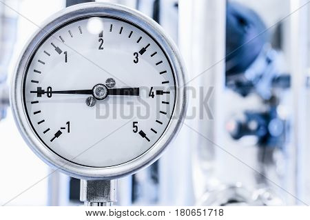 The measuring device is a manometer. White dial with black numerals.