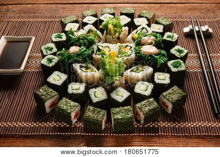 Food art, japanese traditional cuisine. Round ornament of green sushi rolls set served on brown straw mat, closeup. Japanese seafood, culinary masterpiece.