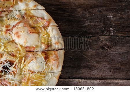 Fresh italian pizza with bacon, ham and cheese served on rustic wooden table, flat lay. Junk food, bad habits, calories. Dark background with free space for text.