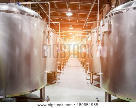 Modern Beer Factory. Steel tanks for beer fermentation and storage. Sunlight effect