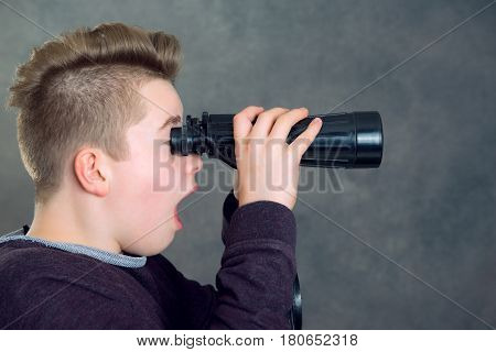 teenage boy looking through a binoculars in front of gray background