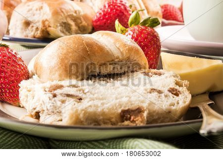 hot cross buns butter and sweet strawberries on a plate