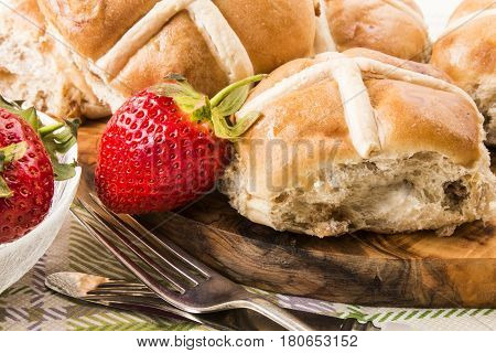 british hot cross buns and sweet strawberries on a wooden board
