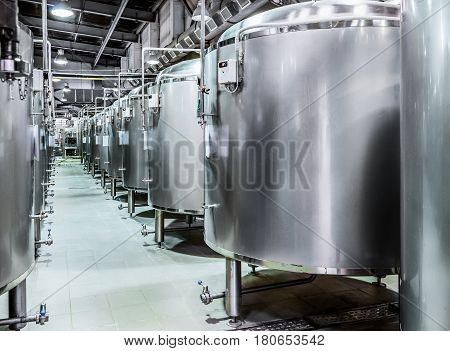 Modern Beer Factory. Rows of steel tanks for beer fermentation and maturation. Toned image.