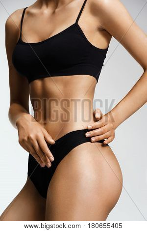 Sporty woman in black lingerie cares about her body. Perfect slim toned young body of the girl. Fitness or body care concept