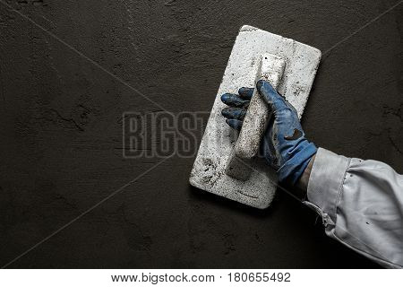 Worker working manual with wall plastering tools inside a house.