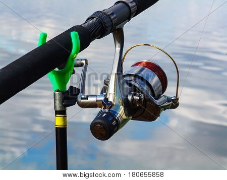 Fishing rod on the stand and coil with the fishing line closeup