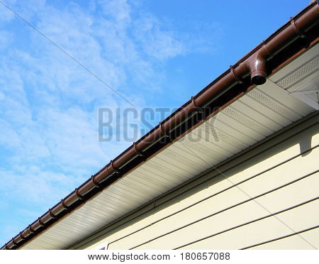 Close up on Rain Gutter Soffit Board Fascia Board Installation Against Blue Sky. Guttering. Roof repair.