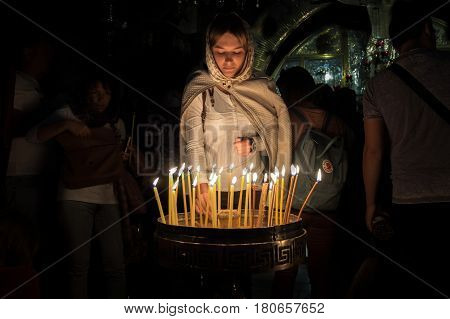 Undefined Girl Light A Candle In The Holy Sepulchre On Mount Calvary, Jerusalem, Israel