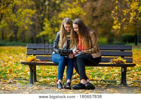 Early warm fall. Two charming girls sit on a bench in the autumn park. They with interest look at the laptop screen. Nearby on a bench bouquets of autumn leaves lie. Ground in the park is covered by the fallen-down foliage.