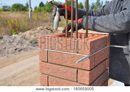 Bricklayer Worker Installing Red Clinker Blocks around Iron Bar and Caulking Brick Masonry Joints Exterior Wall with Trowel Putty Knife and Fixing with Spirit Level Outdoor