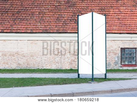 Mock up. Blank outdoor advertising column outdoors, public information board in the city.