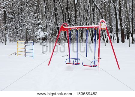Empty Colorful Swing in Winter Time with Snow Outdoor. Children Playground In Public Park Covered With Winter Snow.