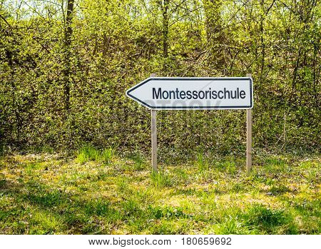 Streetsign indicating the way to a Montessori school in Germany