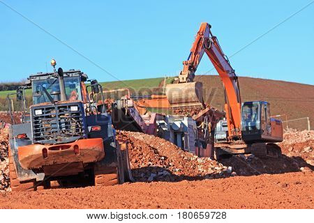 Front loader, digger and stone crusher on a construction site