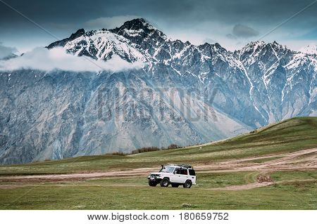 White SUV Car On Off Road In Spring Mountains Landscape In Georgia. Drive And Travel Concept. Landscape Of Gorge At Spring Season.