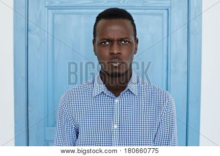Close up moody portrait of distrustful young man looking at camera with skeptical suspicious expression emotion. Young Afro American office man is worry about his salary in front of blue door. Doubt and confusion concept.