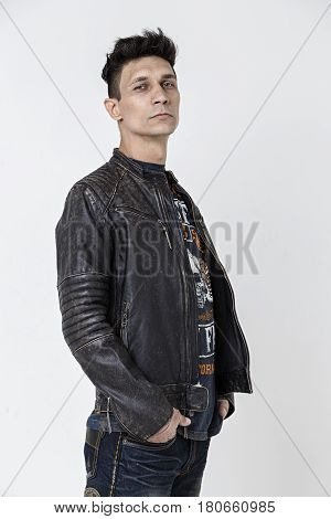 Haughty man in leather jacket on white background photo in studio vertical photo