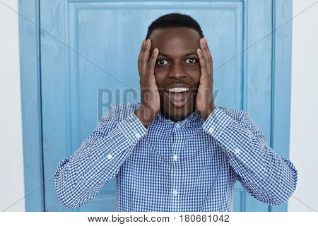 Omg!Astonished young African American office employee or customer with shocked and surprised face looking and wondering at camera with big eyes and mouth wide open holding hands on his cheeks. Human face expressions and emotions.