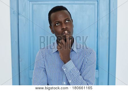 Portrait of young African American man holding hand on his chin looking up with thoughtful and skeptical expression on his face suspecting of something hesitating to make decision. Studio shot on blue door background.