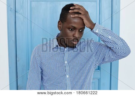 Young african american man holding his hand with quilty face. Portrait of office worker who forget failed something very important or made a big mistake. Negative human emotions and expressions concept.
