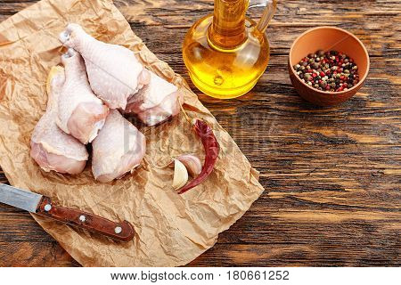 Chicken legs on crafted crumpled paper next are spices on a wooden table top view