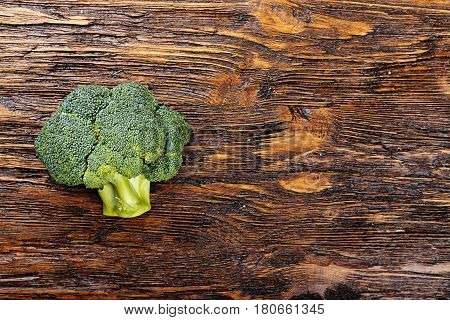 Inflorescence of raw broccoli on a wooden table horizontal photo