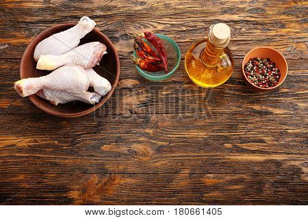 Chicken legs in a clay plate next to the spices on a wooden table top view