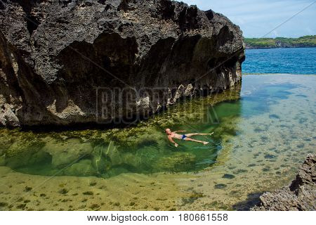 A man swimming in a natural pool with water on the background of the ocean. Angel's Billabong Nusa Penida Indonesia.