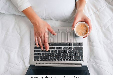 Unrecognizable woman hold cup of morning coffee with laptop on white blanket in bed, top view. Internet addiction, psychological disorder, unhealthy lifestyle concept.