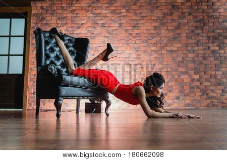 Slender brunette in red little dress lying on a black armchair