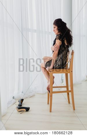 Slender brunette in black little dress sitting on a wooden chair