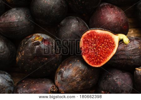 Fresh ripe figs background close-up. Variety of tasty purple fig fruits with one cut. Market, organic food, gourmet, vitamin concept
