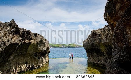 A couple of a guy and a girl are standing over a cliff and looking at the ocean. Angel's Billabong Nusa Penida Indonesia.
